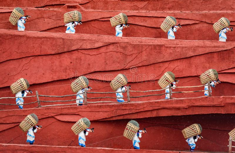 Farmers carrying baskets on back, Lijiang, Yunnan, China. Yunnan, China - 24 March 2016: Female farmers carrying baskets of harvest on back stock photo
