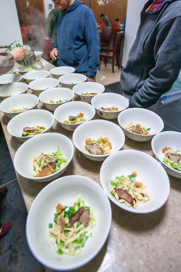 Yunnanese鸡蛋面用猪肉和菜在白色碗,当地食物在云南,中国 库存照片