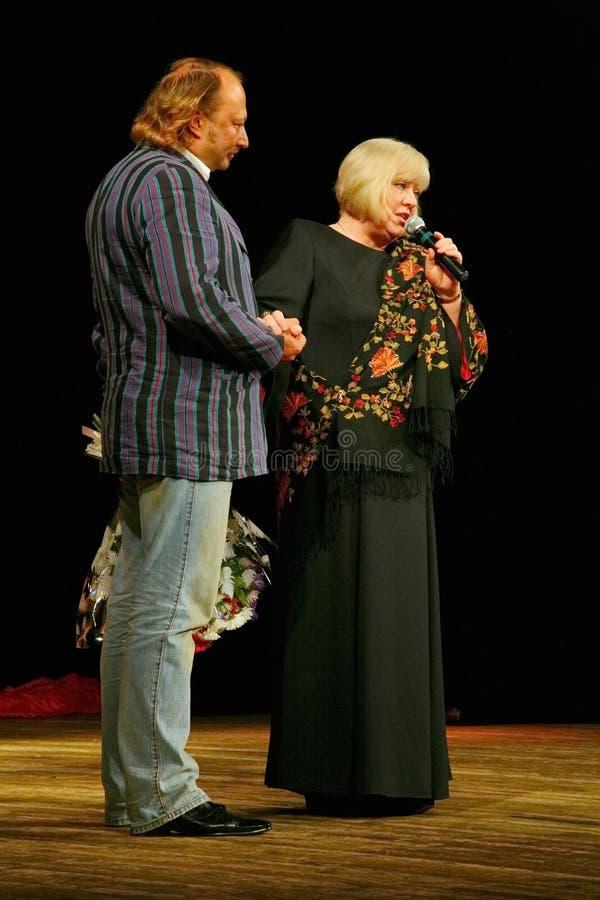 Yuriy Galtsev felicita a Svetlana Kryuchkov en el día de su nacimiento, pronuncia un discurso solemne y da las flores fotografía de archivo libre de regalías