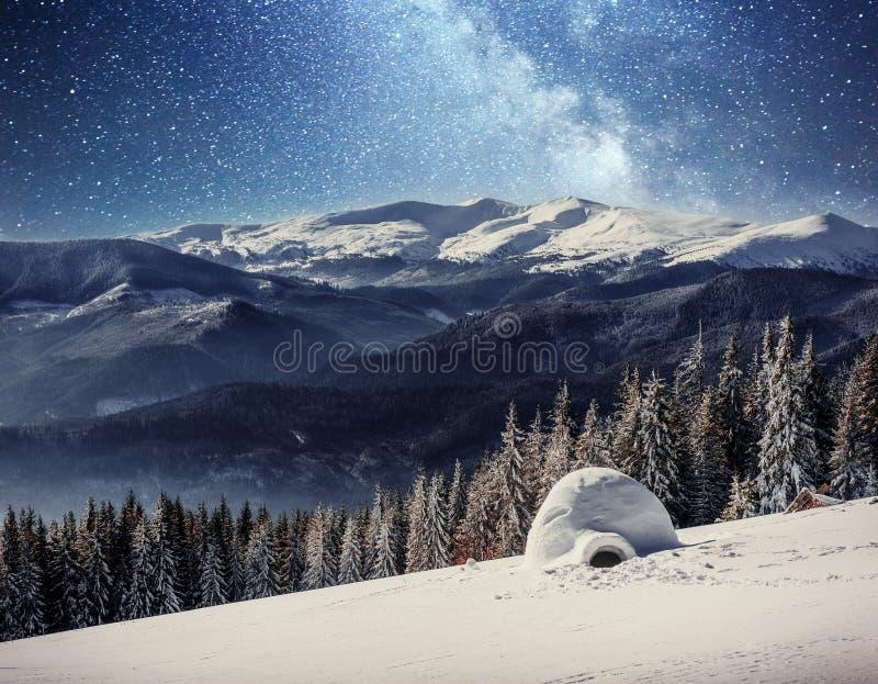 Yurt en la nieve en el cielo estrellado del bosque del invierno sobre los picos de montaña foto de archivo
