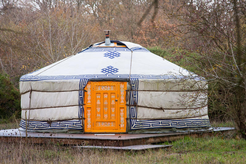 Yurt in a forest. Close-up photo of one white yurt with blue simbols and big closed well-decorated orange door in the forest on an autumn day royalty free stock photos