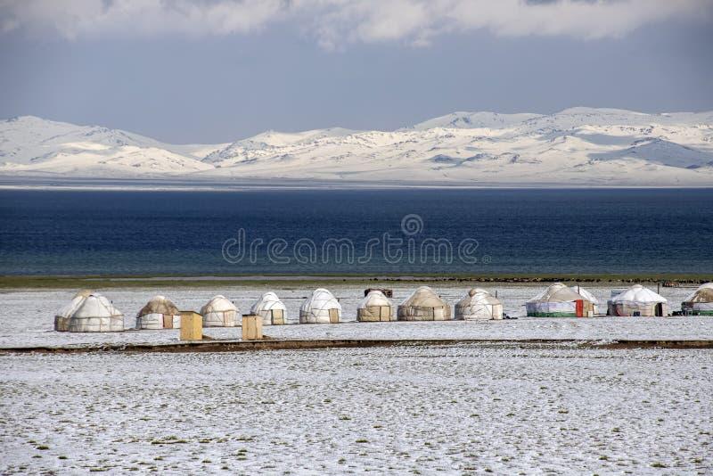 Yurt stad på kusten av son-Kul sjön på bakgrunden av snö-korkade berg Resor kyrgyzstan arkivfoton