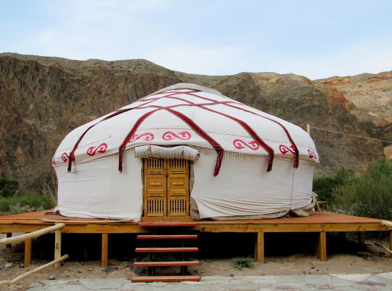 Yurt traditional house. Yurt traditional middle asian house in Kyrgyzstan. White cloth walls, round shape of the house, doors, stairs and wooden stand. Beautiful stock photography