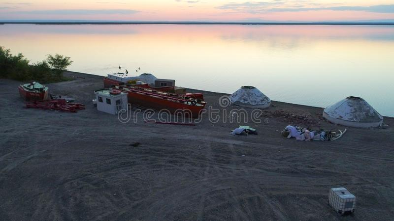 Yurts, βάρκες και άνθρωποι που κολυμπούν κατά τη διάρκεια του ηλιοβασιλέματος στη λίμνη Ailik ή Aylik, στοκ εικόνες