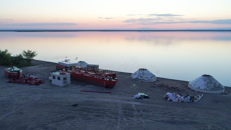Yurts, βάρκες και άνθρωποι που κολυμπούν κατά τη διάρκεια του ηλιοβασιλέματος στη λίμνη Ailik ή Aylik, στοκ εικόνα