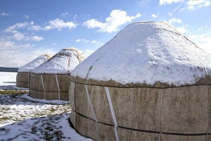 Yurts κάτω από το χιόνι στη μέση ενός χιονισμένου τομέα ενάντια σε έναν ουρανό με τα σύννεφα ταξίδι Κιργιστάν στοκ εικόνα