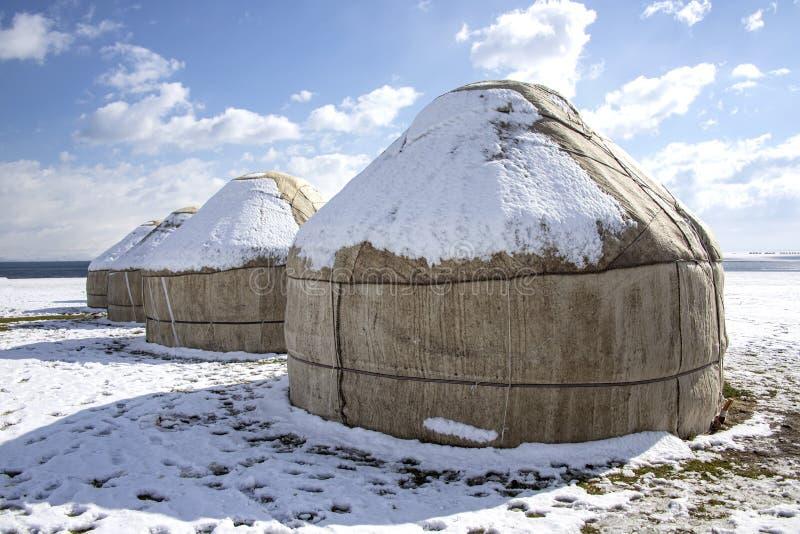 Yurts κάτω από το χιόνι στη μέση ενός χιονισμένου τομέα ενάντια σε έναν ουρανό με τα σύννεφα ταξίδι Κιργιστάν στοκ φωτογραφία
