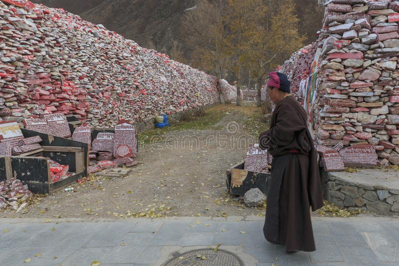 Tibetan monk walking in front of Mani stones wall with buddhist mantra Om Mani Padme Hum engraved in Tibetan in Yushu, China royalty free stock photo