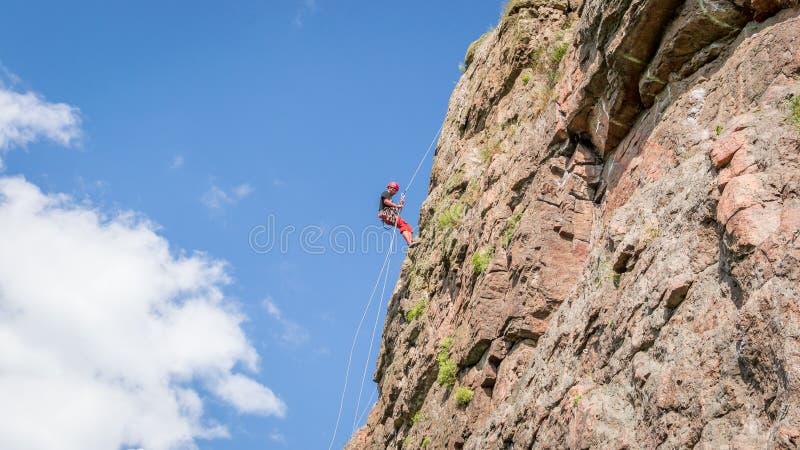 Yuzhnoukrainsk, Украина - 19-ое июня 2018: Скалолазание Молодой альпинист взбирается вертикальный утес гранита весьма спорт стоковые фото