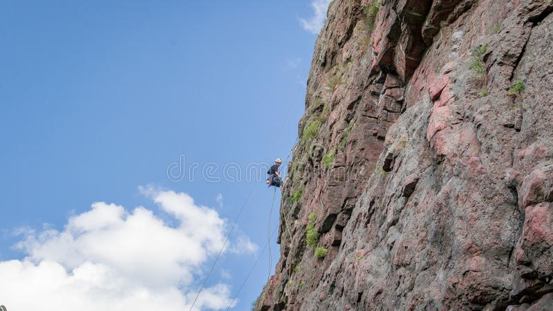 Yuzhnoukrainsk, Ucrania - 19 de junio de 2018: Escalada Un escalador joven sube una roca vertical del granito Deporte extremo fotos de archivo libres de regalías