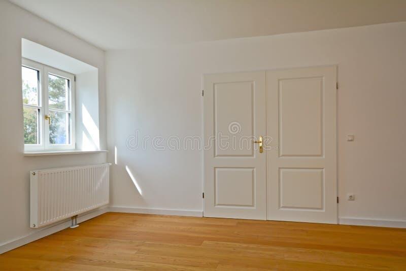 Żywy pokój mieszkanie z dwoistym drzwi i parkietowa podłoga po odświeżania w starym budynku - zdjęcie stock