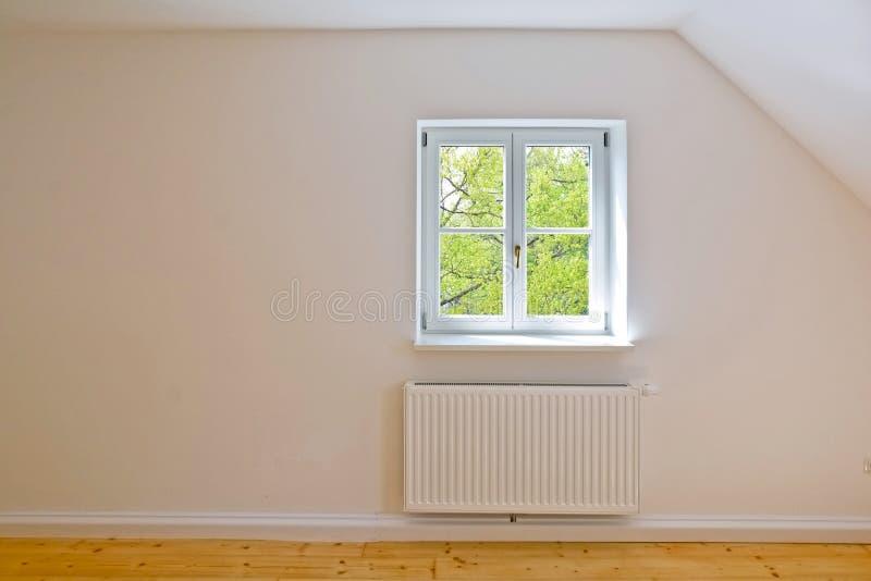 Żywy pokój na najwyższym piętrze, mieszkaniu z drewnianymi okno i parkietowej podłoga po odświeżania, zdjęcie royalty free