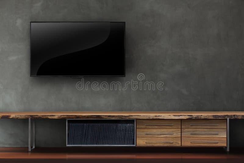 Żywy pokój prowadził tv na betonowej ścianie z drewnianym stołowym medialnym furn zdjęcie stock