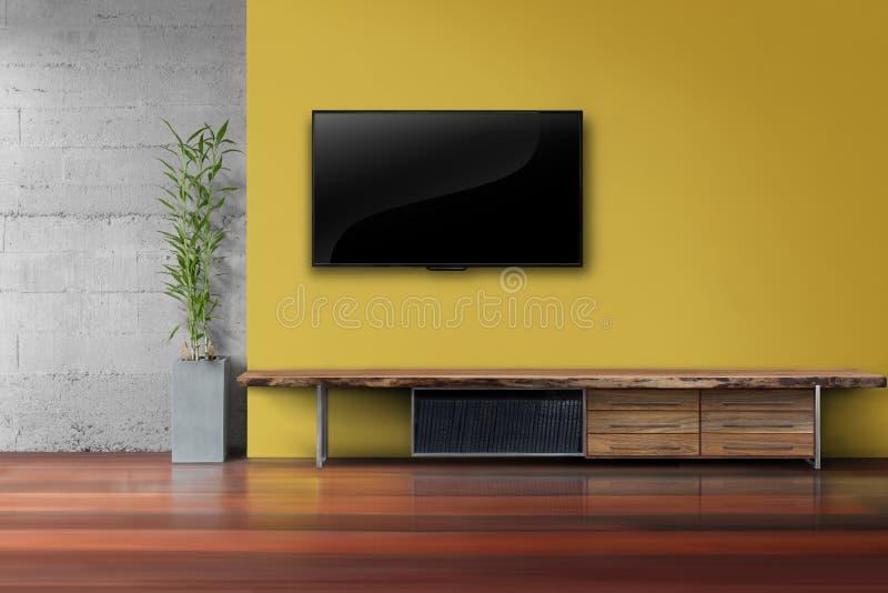 Żywy pokój prowadził tv na kolor żółty ścianie z drewnianym stołowym medialnym furnit zdjęcie stock