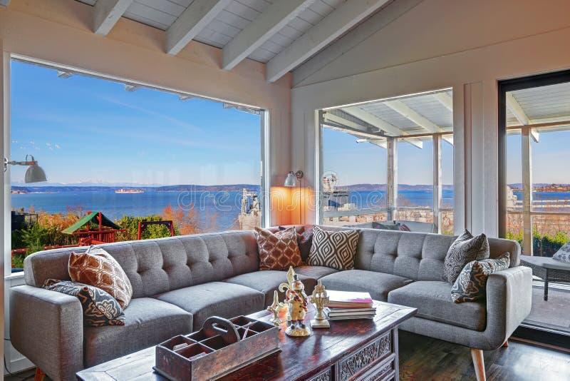 Żywy pokój z wodnym widokiem i ampuły popielatą nowożytną kanapą zdjęcie royalty free