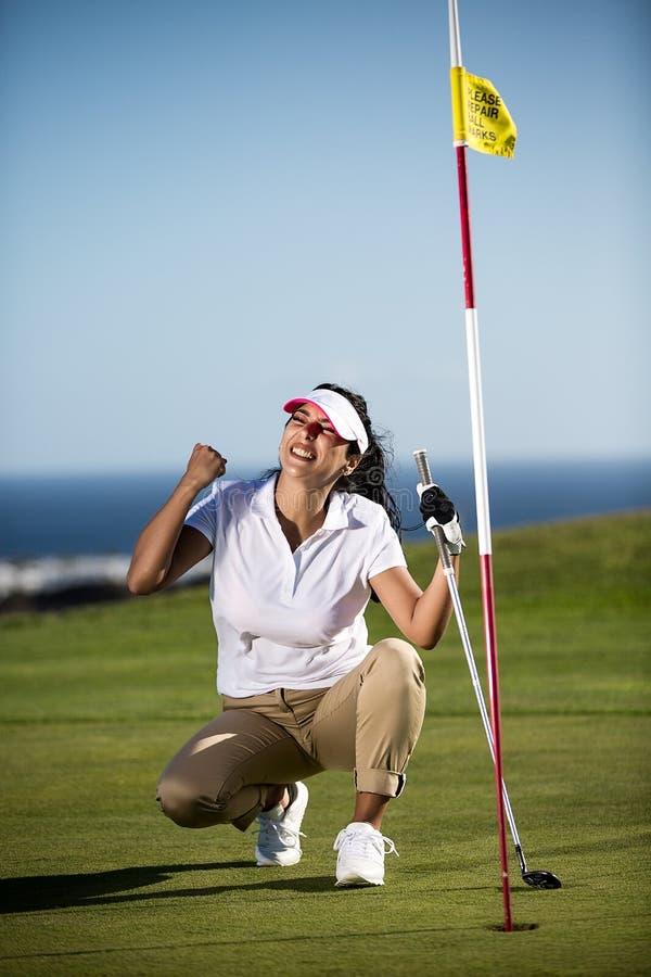 Zählendes Ziel der aufgeregten Frau auf Golffeld lizenzfreie stockbilder