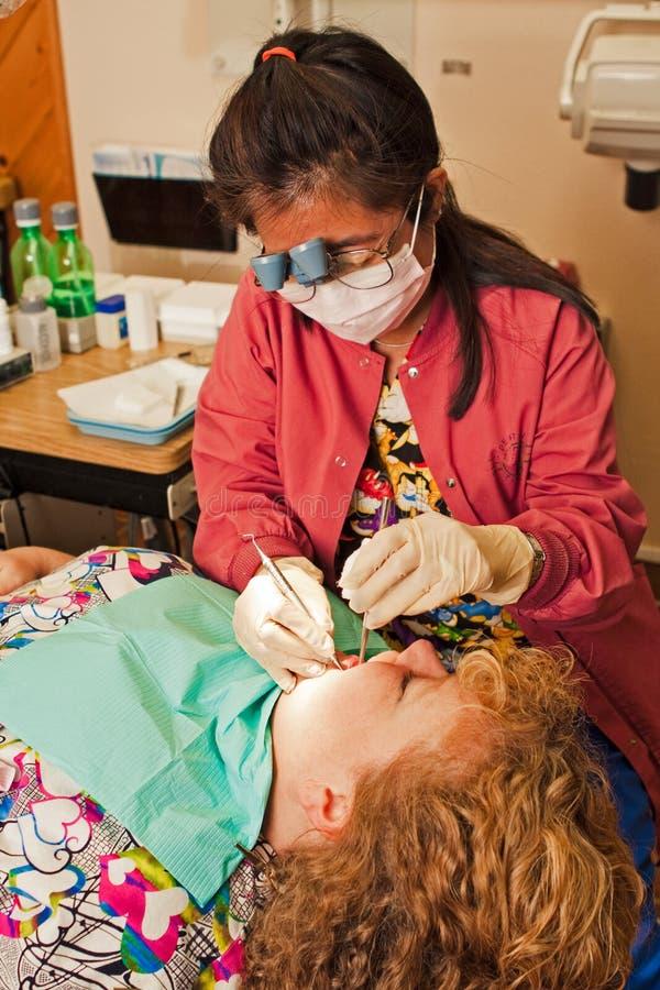 Zähne des Zahnarzthelferreinigungspatienten lizenzfreies stockbild