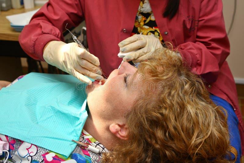 Zähne des Zahnarzthelferreinigungspatienten stockbild