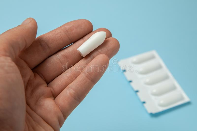 Zäpfchen für analen oder vaginalen Gebrauch in den Händen eines Mannes Kerzen für Behandlung von Hämorriden, Temperatur, Drossel lizenzfreies stockfoto