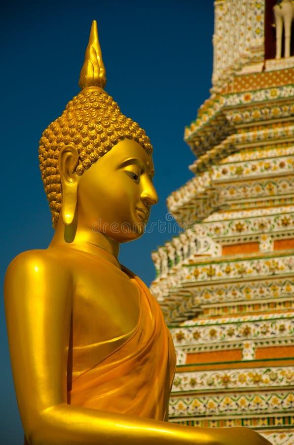 Złota żółta statua medytuje i ono modli się Buddha obsiadanie zdjęcia royalty free