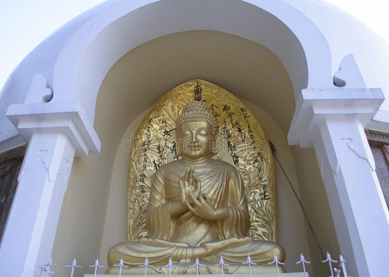 Złota statua władyki Buddha obsiadanie w wysokiej scenie fotografia stock
