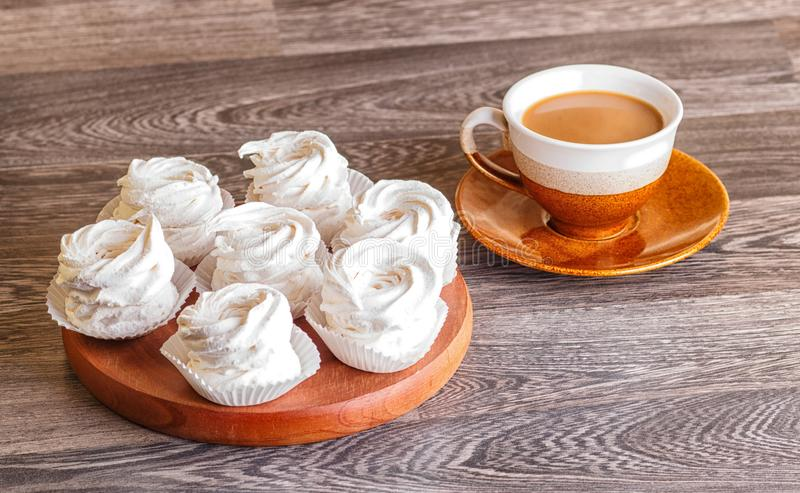 Zéfiro branco dos marshmallows em uma placa de madeira redonda com o copo de imagem de stock royalty free