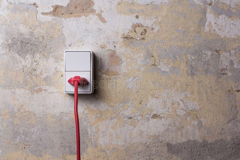 Zócalo con el alambre rojo en la pared sucia imagen de archivo
