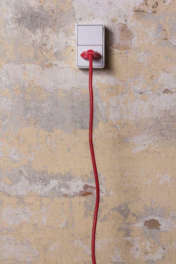Zócalo con el alambre rojo en la pared sucia fotos de archivo