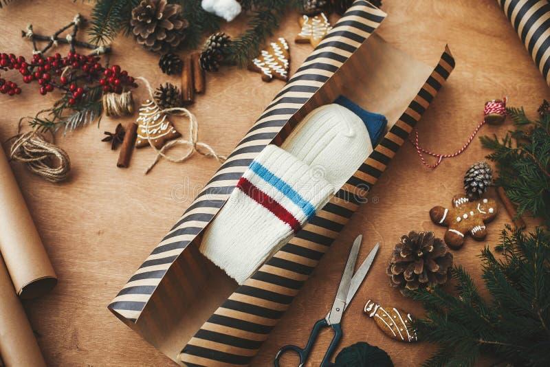 Zócalos de elegante papel de envolver a rayas, acogedores regalos de Navidad y ramas de pino, conos, galletas de jengibre, hilo,  foto de archivo libre de regalías