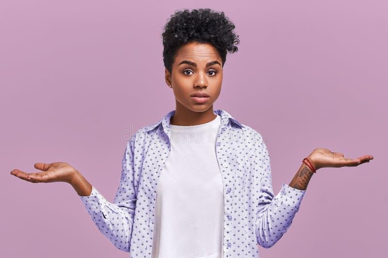 Zögernde verwirrte junge Frau mit Afrohaarschnitt, zuckt Schultern und stellt Dilemma, schaut ahnungslose Nebenwirkung, hält Händ lizenzfreie stockfotos