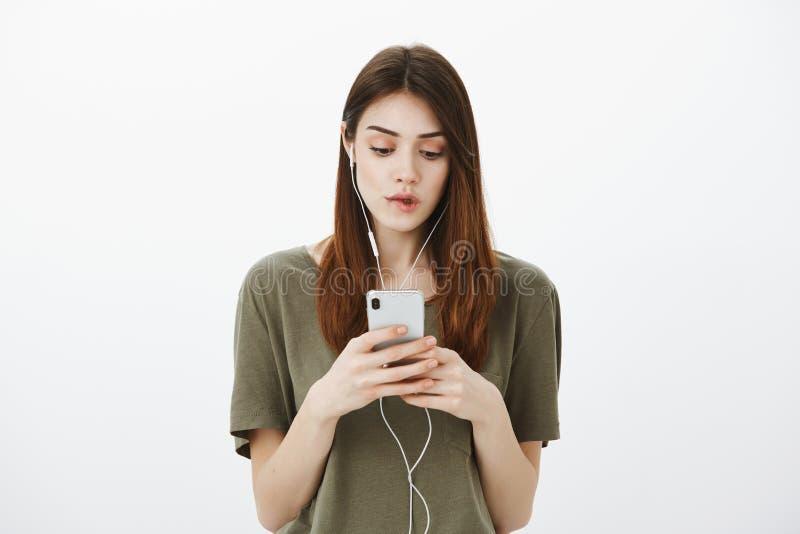 Zögerndes Mädchen bei der Erfassung des ex Freundes des Muttelefons Zweifelhafte besorgte attraktive weibliche, beißende Lippe un lizenzfreie stockfotografie