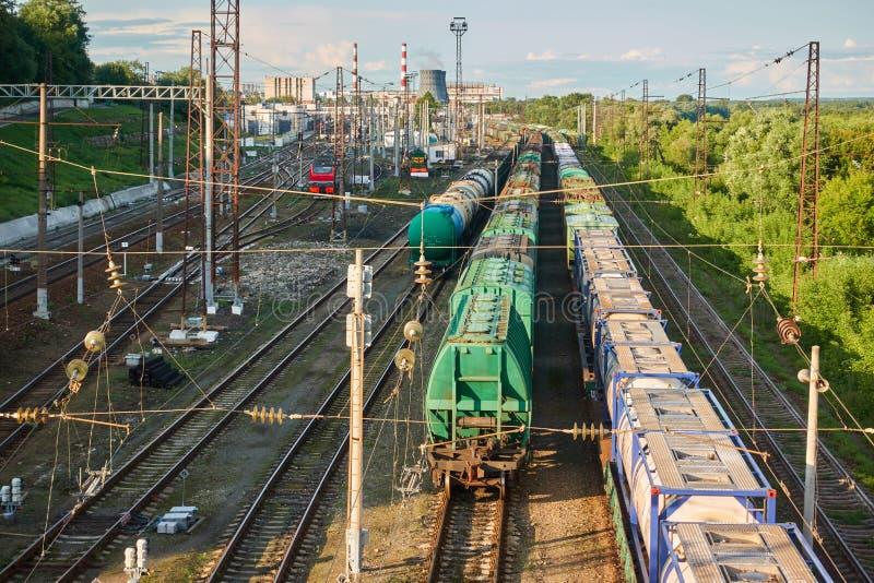 Züge auf der Eisenbahn mit der Fabrik im Hintergrund Schie?en von der H?he stockbilder