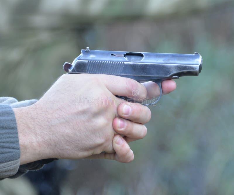 Zündung von zwei Händen von einer Makarow-Pistole stockfotos