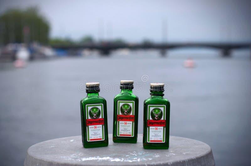 Zürich, die Schweiz - 2019, am 20. Juni: Flasche 3 von Jagermeister auf Flussseite Alkoholgetr?nk mit Kr?utern und Gew?rzen auf b lizenzfreie stockfotografie