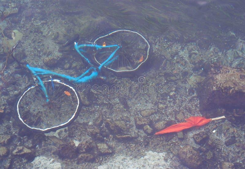 Zürich, Zwitserland - 2019, 20 Juni: Blauwe fiets en oranje paraplu onder het water royalty-vrije stock fotografie