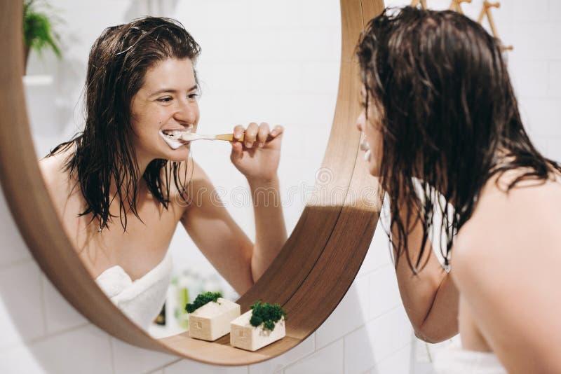 Ząb opieki pojęcie Młoda szczęśliwa kobieta szczotkuje zęby i patrzeje round lustro w eleganckiej łazience w białym ręczniku Szcz fotografia royalty free