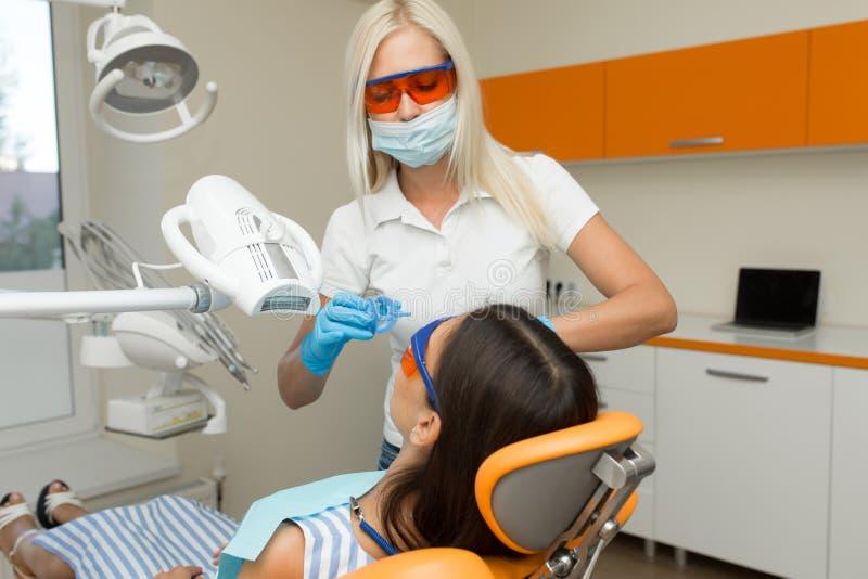 Zęby bieleje stomatologicznym ULTRAFIOLETOWYM dobieranie przyrządem, stomatologiczny asystent bierze opiekę pacjent, oczy ochrani zdjęcie stock