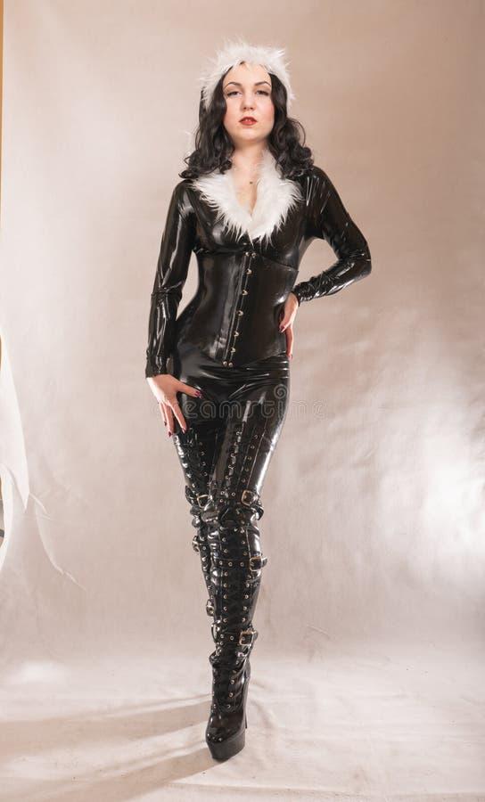 Zła kinky czarna satna dziewczyna pozuje w lateksowym gumowym kostiumu z białym futerkiem na ciemnym kolorowym pracownianym tle obraz royalty free