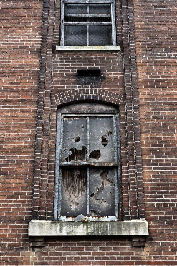 Złamane okna w opuszczonym budynku fabryki cegieł w mieście obrazy royalty free