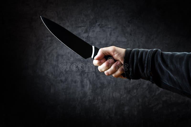 Złego mężczyzna chwyta błyszczący nóż, zabójca w akci obrazy royalty free