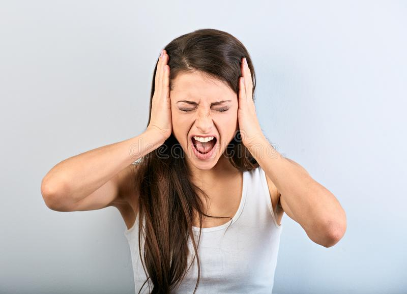 Złości biznesowej kobiety młody silny krzyczeć z dzikim otwartym usta i trzymać głowę ręki na błękitnym tle zdjęcia royalty free