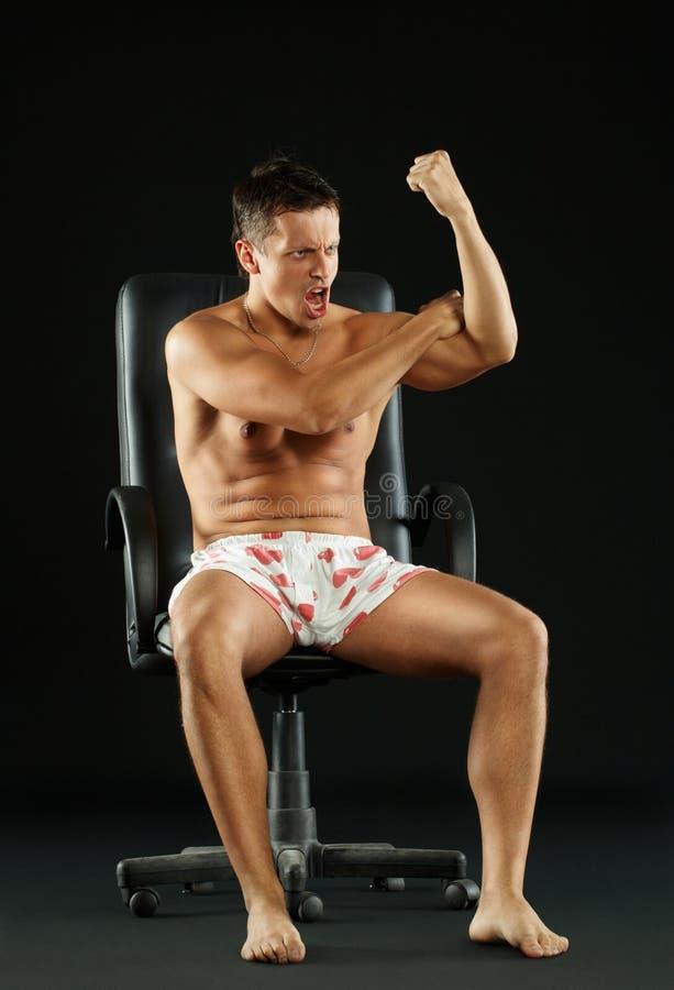Złośliwy mężczyzna obsiadanie na krześle obraz stock