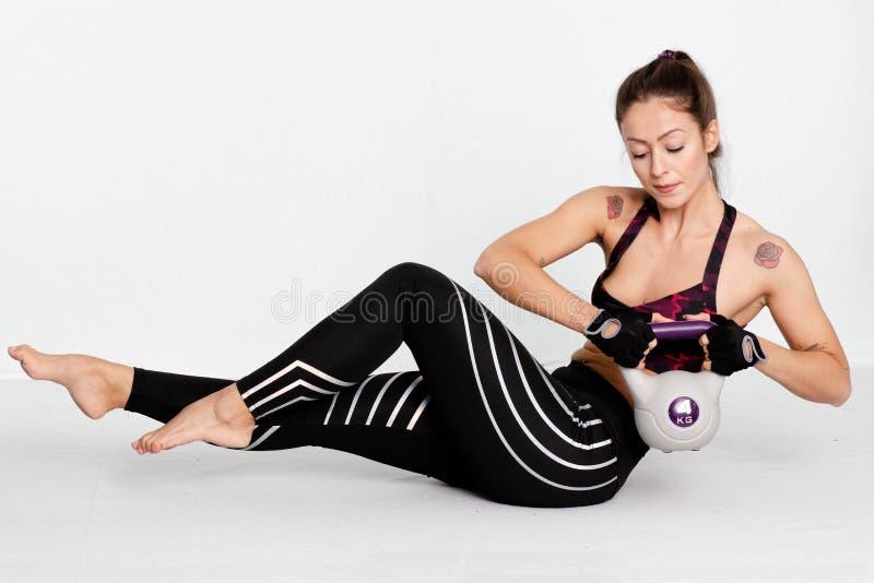 Złożony wizerunek ćwiczy z kettlebell mięśniowa kobieta niezrównoważenie zdjęcia royalty free