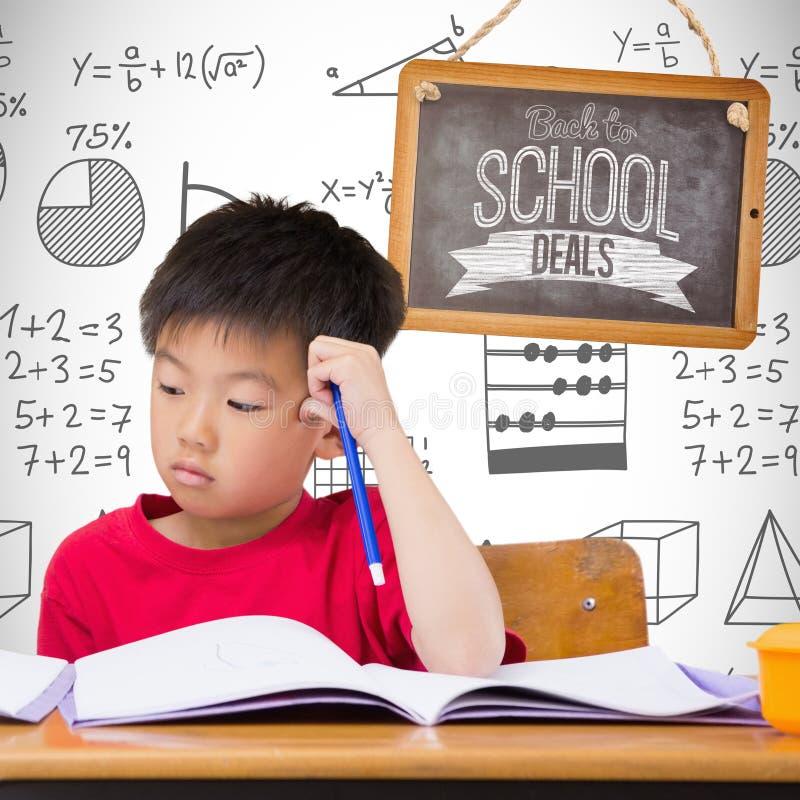 Złożony wizerunek śliczni ucznie pisze przy biurkiem w sala lekcyjnej obraz stock