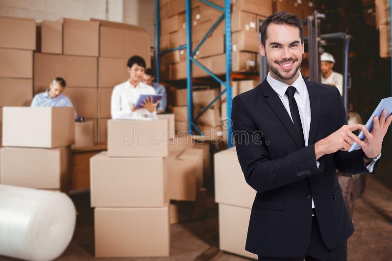 Złożony wizerunek biznesmen używa jego pastylkę podczas gdy patrzejący kamerę obrazy royalty free