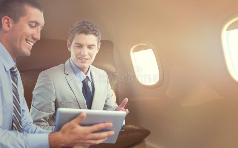 Złożony wizerunek biznesmeni pracuje wraz z laptopem i pastylką obraz stock