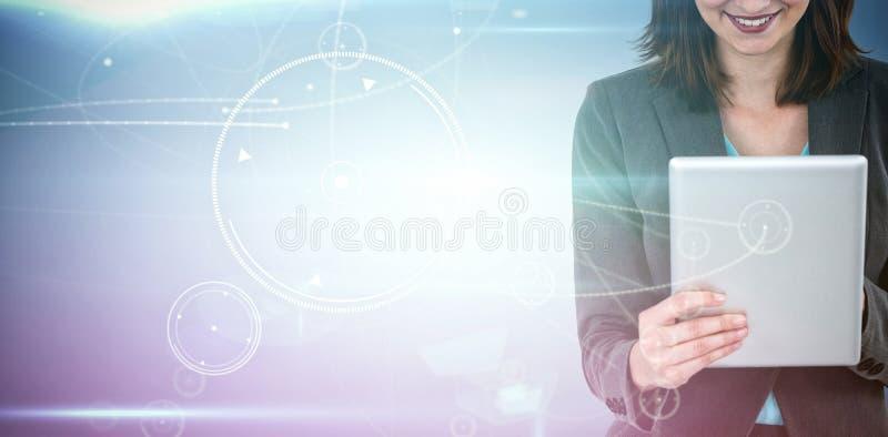 Złożony wizerunek bizneswoman używa pastylkę zdjęcie stock