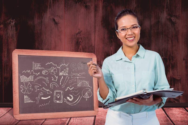 Złożony wizerunek jest ubranym szkła bierze notatki w jej schowku poważny bizneswoman fotografia royalty free