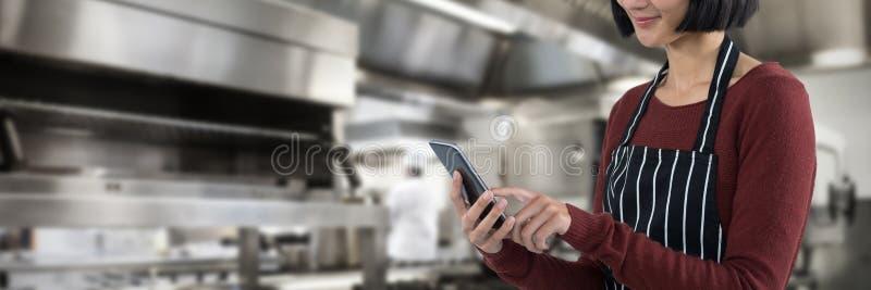 Złożony wizerunek kelnerka używa telefon komórkowego przeciw białemu tłu obraz stock