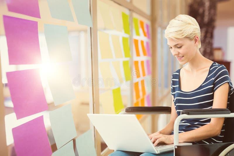 Złożony wizerunek kobieta w wózku inwalidzkim używać komputer obraz stock